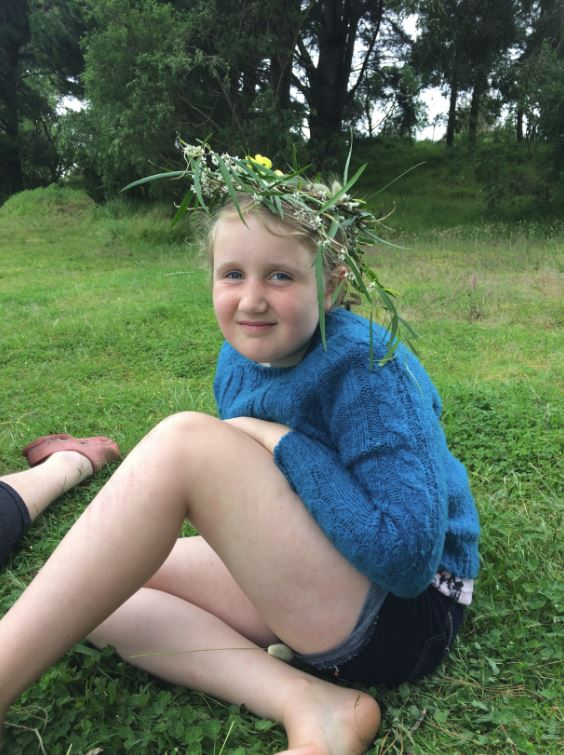 "Lola says: ""In November, we had an overnight camp with KCC at Wiritoa Lake. We had a fire and toasted marshmallows. There was a swing going over the lake as well as three other playground swings. Here I am wearing a wreath I made at camp."""