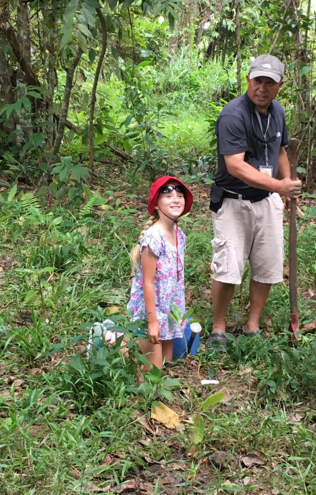 Alexis and guide Bryant planting native trees beside the Kinabatangan River.